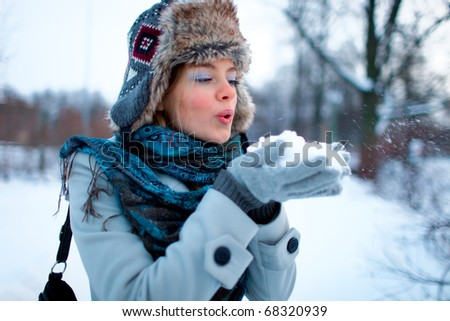 Portrait of beautiful young girl blowing on snow - stock photo