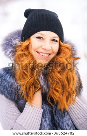 Portrait of beautiful young girl dressed in fur coat at winter background. Beauty woman having fun outside on winter snowy day. Close up of female smiling face with gorgeous long red hair.  - stock photo