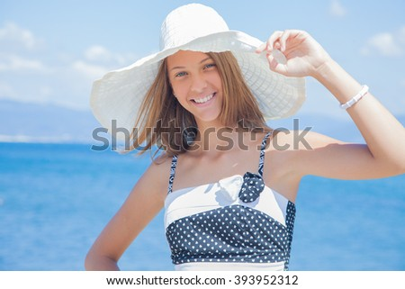 portrait of  beautiful young girl in a dress on a background of the sea