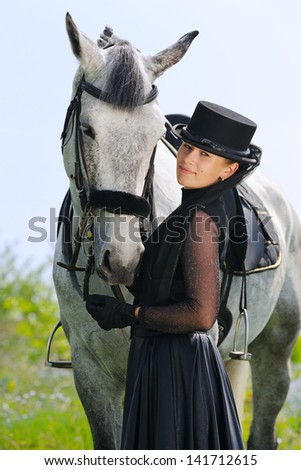 Portrait of beautiful young girl in black dress  with horse