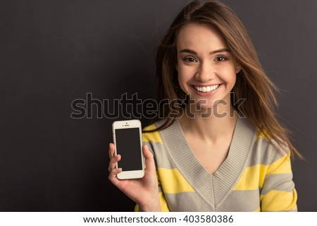Portrait of beautiful young girl in casual clothes showing a smartphone, looking at camera and smiling, against dark background - stock photo