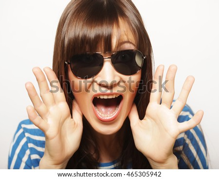 Portrait of beautiful young girl in sunglasses a look of surprise