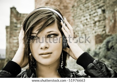 portrait of beautiful young girl in town listening to music with headphones - stock photo
