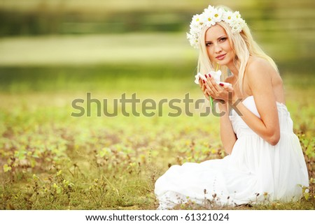 Portrait of beautiful young girl sitting in grass - stock photo