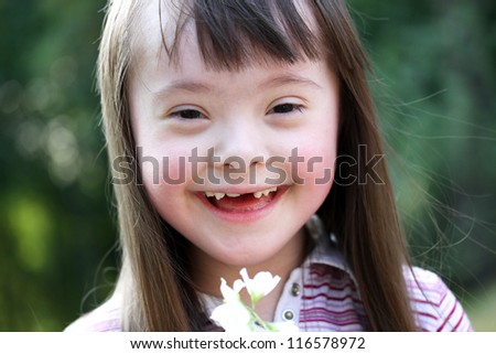 Portrait of beautiful young girl smiling with flowers in the park - stock photo