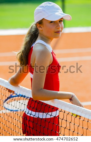 Portrait of beautiful young girl tennis player on the court.