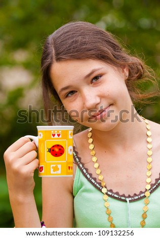 Portrait of beautiful young girl with a yellow cup outdoors - stock photo
