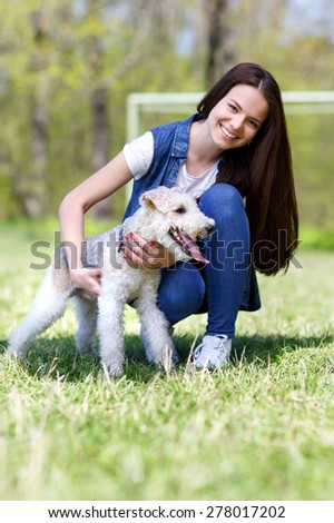 portrait of Beautiful young girl with foxterrier dog  outdoor in  park - stock photo