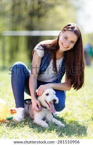 portrait of Beautiful young girl with foxterrier dog outdoor in  park