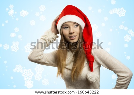 portrait of beautiful young girl with funny red christmas hat . She posing with long smooth hair, warm sweater and smiling