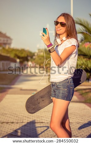 Portrait of beautiful young girl with skateboard and headphones looking her smartphone outdoors. Warm tones edition. - stock photo