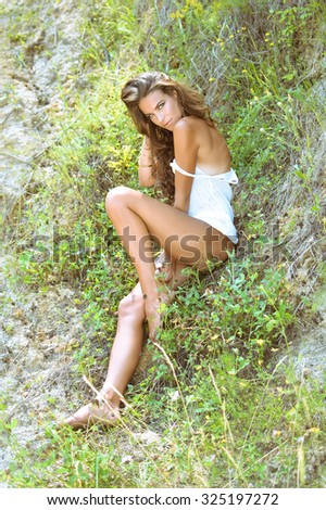 Portrait of beautiful young glamour lady in white top lying on grass. Sexy fashion girl with naked legs and shoulder looking at camera on sunny hillside background. - stock photo