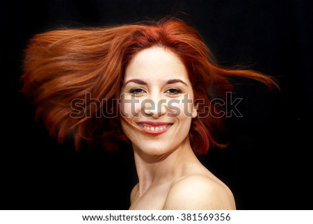 Portrait of Beautiful Young Haired Woman Shaking Her Hair Over Black Background