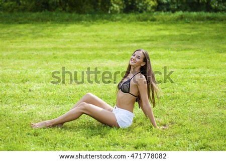 Portrait of beautiful young happy brunette woman sitting on the green grass in summer park