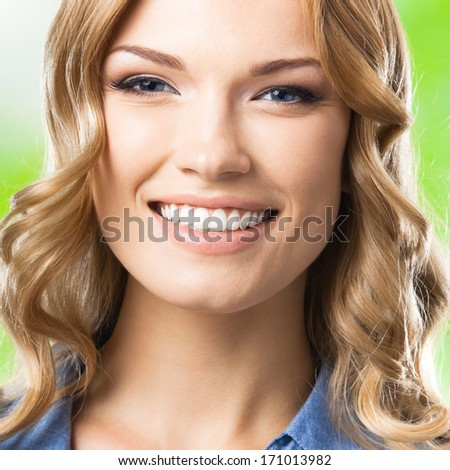 Portrait of beautiful young happy smiling blond woman, giving hand for handshaking, outdoors