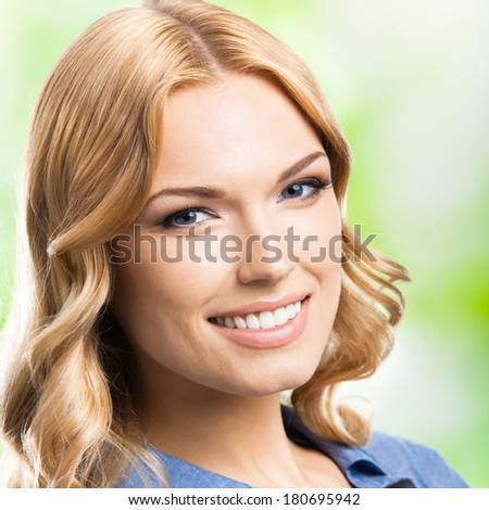Portrait of beautiful young happy smiling blond woman with long hair, outdoors