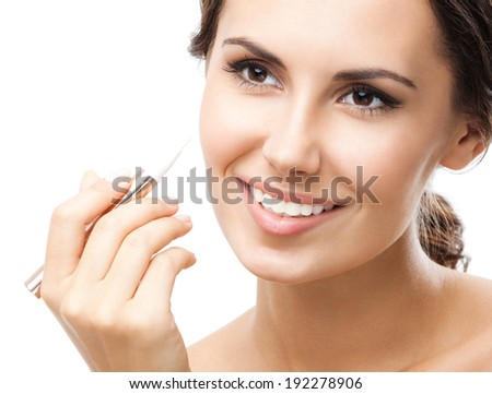 Portrait of beautiful young happy smiling woman applying concealer on face, isolated over white background - stock photo