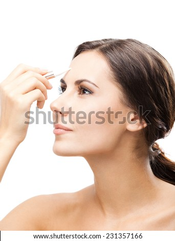 Portrait of beautiful young happy smiling woman applying concealer on face, isolated over white background