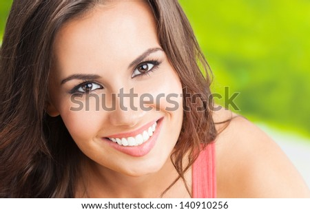 Portrait of beautiful young happy smiling woman, outdoors