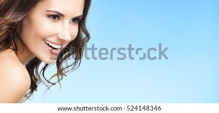 Portrait of beautiful young happy smiling woman, over blue background, with copyspace for slogan or text message. Caucasian brunette model in beauty concept shot.