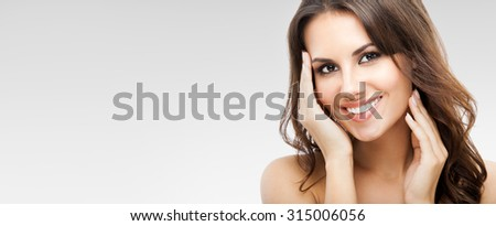Portrait of beautiful young happy smiling woman with long curly hair, over grey background, with copyspace - stock photo