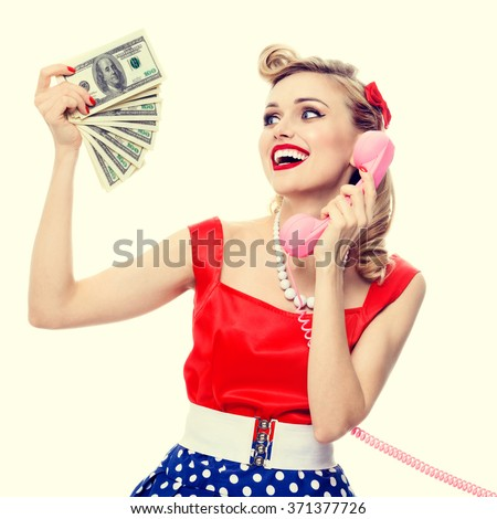 Portrait of beautiful young happy woman with money, talking on phone, dressed in pin-up style dress in polka dot. Caucasian blond model posing in retro fashion and vintage concept studio shoot.