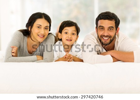 portrait of beautiful young indian family relaxing on bed - stock photo