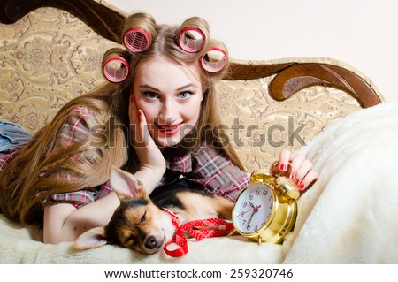 Portrait of beautiful young lady having fun happy smile relaxing lying in bed with clock and her dog - stock photo