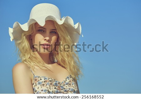 Portrait of beautiful young lady with long blond curly hair and blue eyes wearing white sun hat with wavy brim over clear blue sky. Copy space. - stock photo