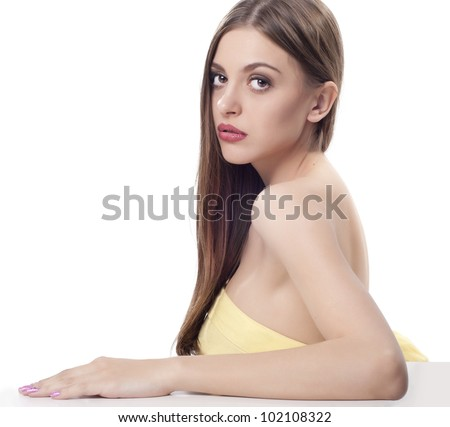 Portrait of beautiful young lady with long dark hair sitting at the table - stock photo