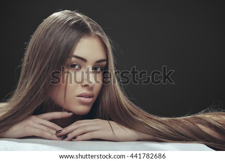 Portrait of beautiful young lady with long silky straight brown hair posing in studio over dark grey background. Hair health, hair freshness, hair care. - stock photo