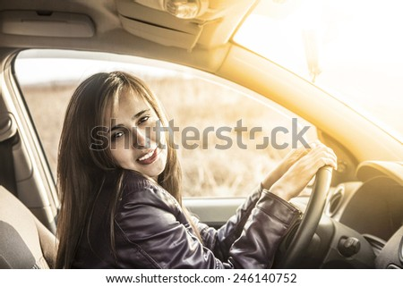 Portrait of beautiful young latin hispanic woman in the new car - indoor talking to an imaginary police, companion, companion, who asks for directions or the right to drive and Documents - stock photo