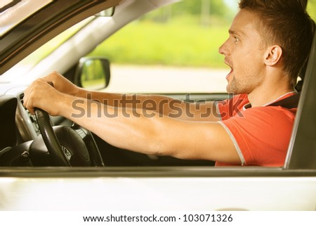 Portrait of beautiful young man in car shocked.