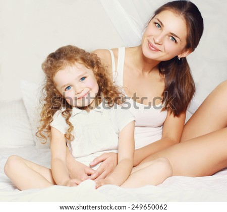 Portrait of beautiful young mother and daughter on the bed - stock photo