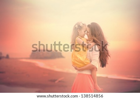Portrait of beautiful young mother and little daughter on the beach, smile and hug - stock photo
