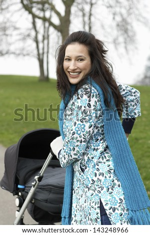 Portrait of beautiful young mother walking with baby carriage in park - stock photo