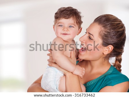 Portrait of beautiful young mother with cute adorable son having fun at home, with pleasure spending time, happy family life
