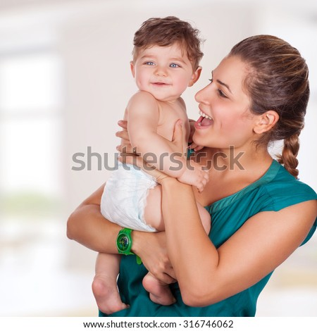 Portrait of beautiful young mother with cute adorable son having fun at home, with pleasure spending time, happy family life - stock photo