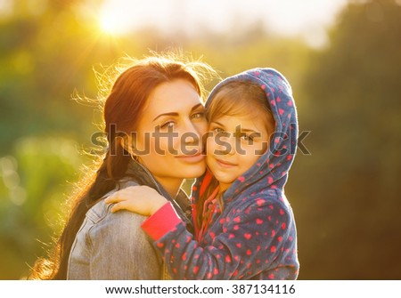 Portrait of beautiful young mother with her cute little daughter outdoors in bright sun light, spending time together in the park, happy loving family - stock photo