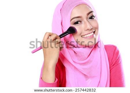 portrait of beautiful young muslim woman applying blush on with white background - stock photo