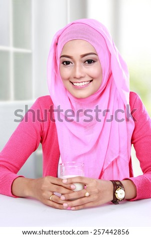 portrait of beautiful young muslim woman had a glass of milk for breakfast - stock photo
