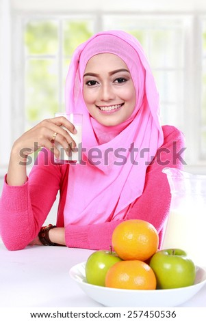 portrait of beautiful young muslim woman had a milk and fruits for breakfast - stock photo