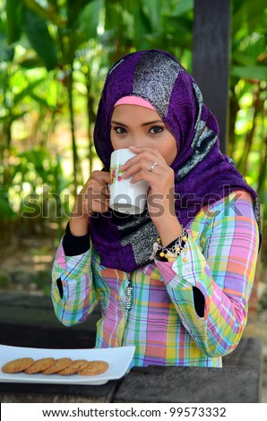 Portrait of beautiful young muslim woman having cup of tea at the park