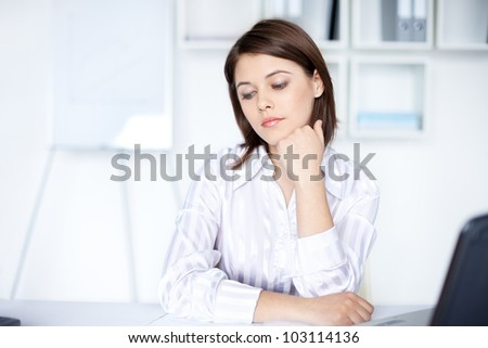 Portrait of beautiful young pensive business woman at office - stock photo