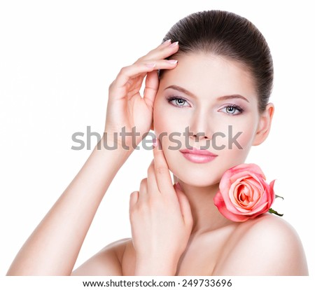 Portrait of beautiful young pretty woman with healthy skin and pink rose near face - isolated on white. - stock photo