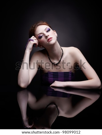 portrait of beautiful young red-haired woman at dark mirror table - stock photo