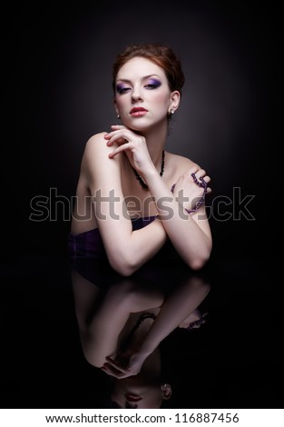 portrait of beautiful young redhead woman sitting at dark mirror table - stock photo