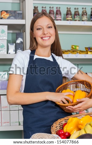 Portrait of beautiful young saleswoman holding vegetable basket in grocery store - stock photo