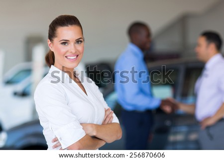 portrait of beautiful young saleswoman standing inside vehicle showroom - stock photo