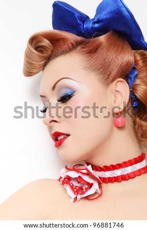 Portrait of beautiful young sexy pin-up girl with sparkly make-up and vintage hairstyle, over white wall - stock photo